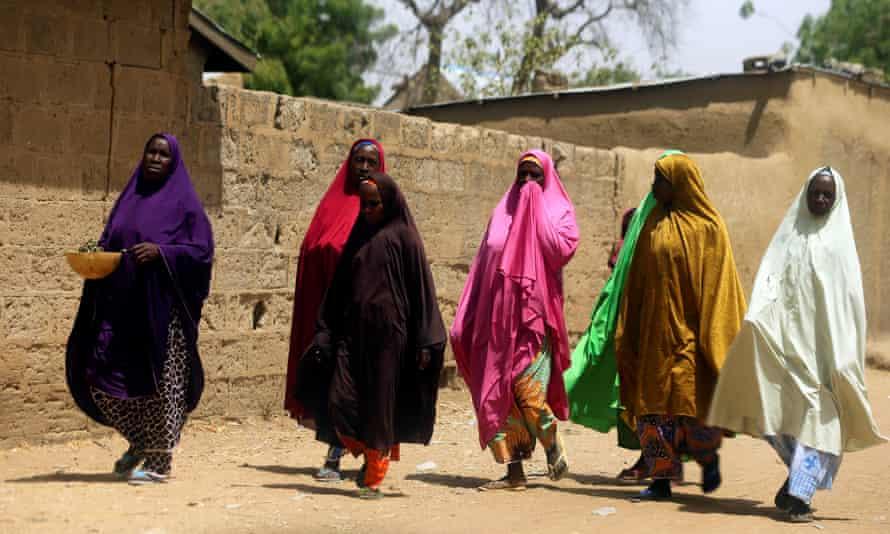 Women walk along a street of Dapchi, a village in Yobe state, Nigeria