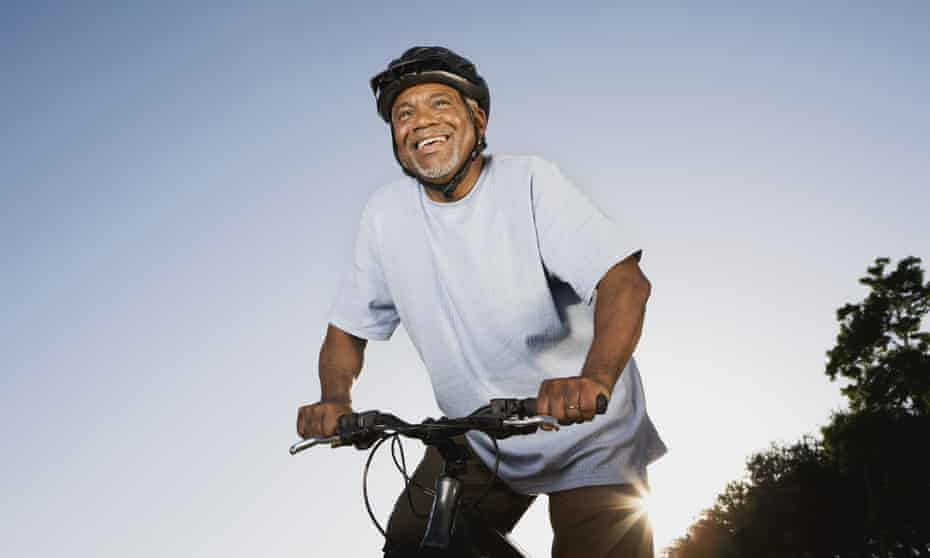 A smiling man riding a mountain bike.