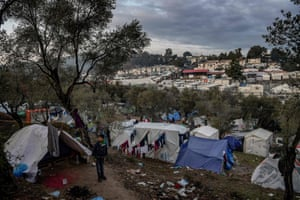 A young boy stands outside a tent at a makeshift camp next to Moria