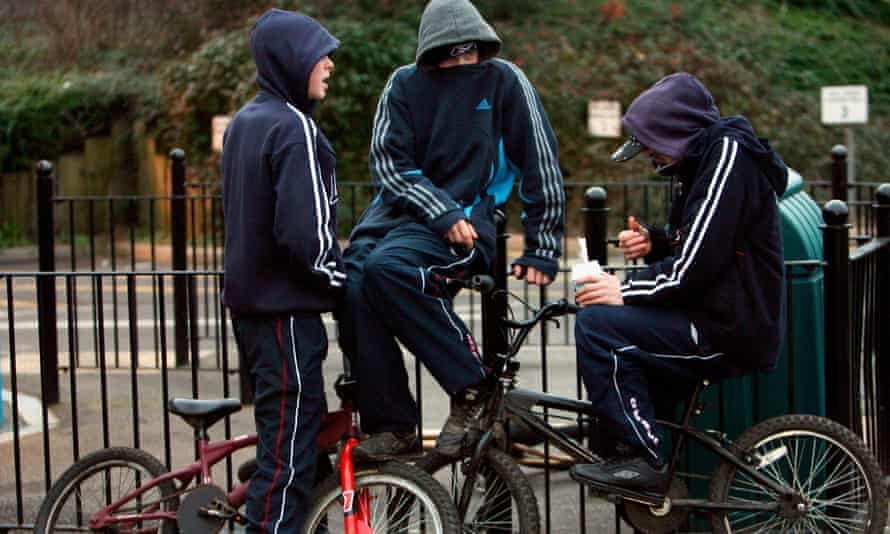 three young boys on bikes with hoodies