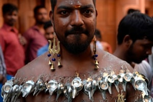 A Hindu devotee with his body pierced with paladais participates in a procession  during the Shivratri festival