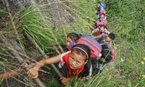 Children of Atule'er Village climb the vine ladder on a cliff on their way home in Zhaojue county.