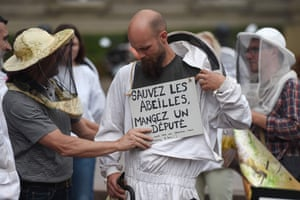 A beekeeper with a placard on his chest reading 'Save a bee, eat a MP' gathers with others during a demonstration in Strasbourg