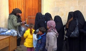 In this photo released by a militant website, members of Islamic State group distribute niqabs to women in Mosul.