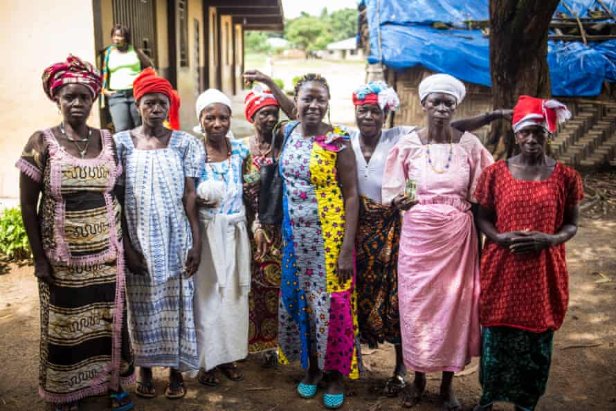 A group of soweis, the most senior women in the Bondo secret societies. The chiefdom's head sowei is Jeanette Bangura (white hat and pink dress). In the centre. wearing a yellow and blue dress, is Ann-Marie Caulker, an anti-FGM campaigner.