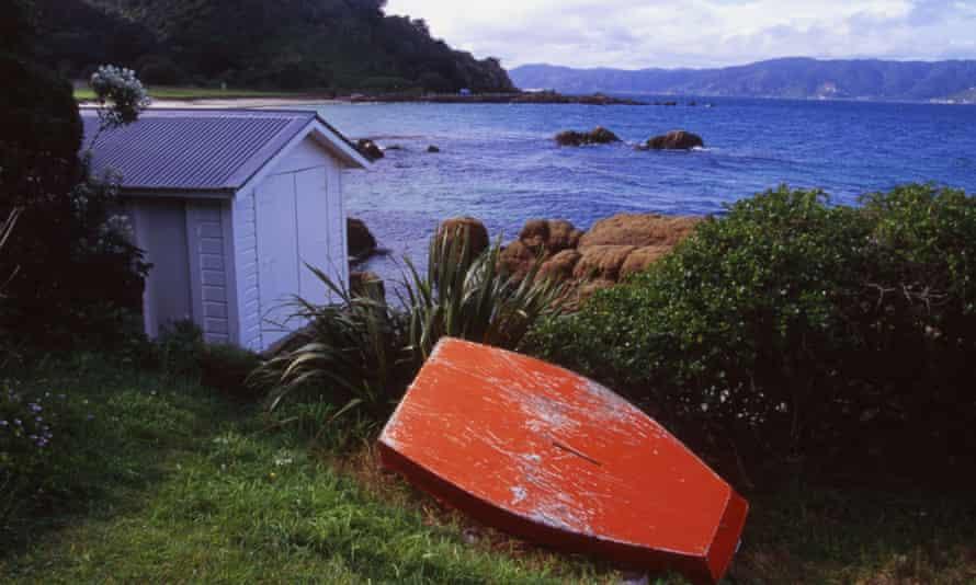 AKMJF7 Boatshed and Upturned Boat Scorching Bay Wellington New Zealand