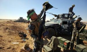 An Iraqi policeman inspects his weapon at the Qayyarah military base