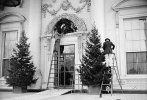 1939 - Workers decorate the White House with Christmas trees and a wreath.