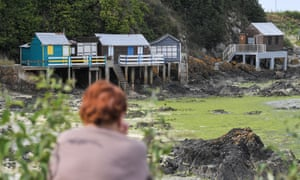 A woman looks at properties declared out of bounds due to algae at the Valais beach in Saint-Brieuc.