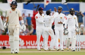 Sri Lanka's captain Dinesh Chandimal (second right celebrates with his teammates after taking the catch to dismiss England's Sam Curran as the England batsman trudges off the pitch.