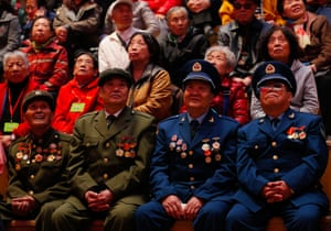 War veterans and local residents watch the opening on television at a bookstore in Shenyang in China's north-eastern Liaoning province