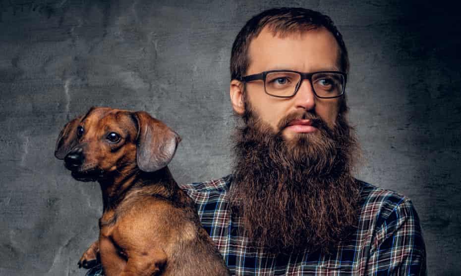 A man with a beard holding a dog