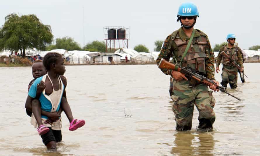 A girl holding a child walks past UN peacekeepers after heavy rains and floods force hundreds of thousands of people to leave their homes in the town of Pibor, Boma state, South Sudan