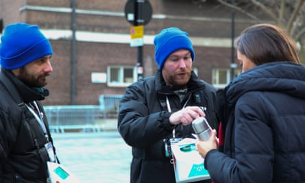 Liam and Danny, vendors for TAP London, speak to a passerby in London.