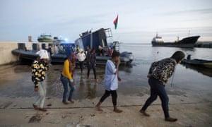 People disembark a Libyan navy boat in  Tripoli