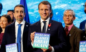emmanuel macron attending a climate event and holding a sign saying make our planet great again