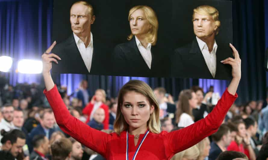 A placard with portraits of Vladimir Putin, Marine Le Pen and Donald Trump is brandished by a journalist at Moscow's World Trade Centre in December 2016