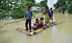 Villagers row a makeshift raft through a flooded field to reach a safer place in Morigaon district.