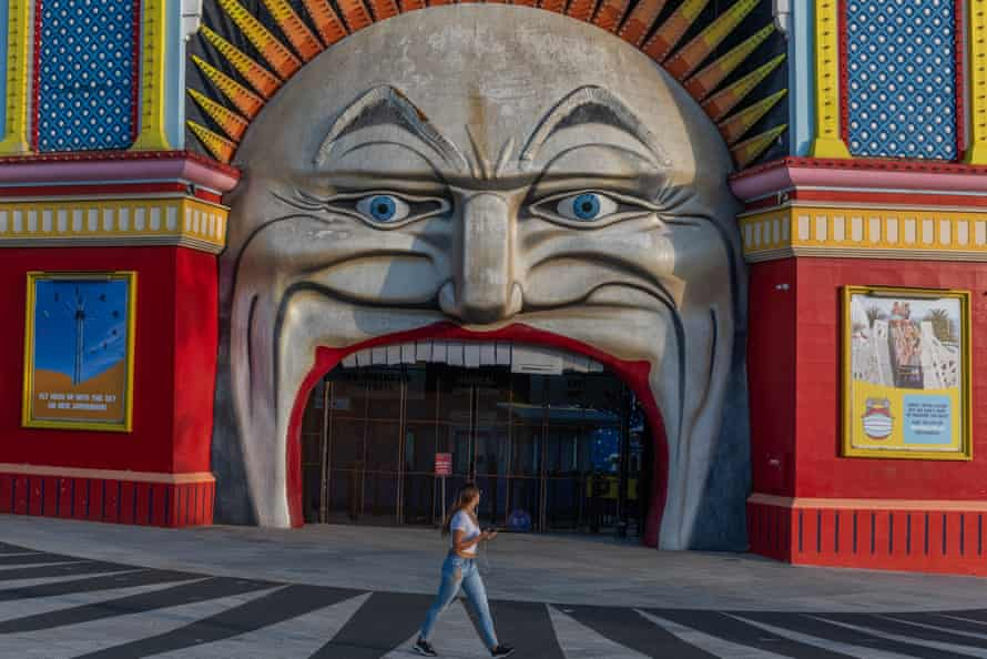 A lone person walks past the Iconic entrance of the now closed Luna Park on March 28, 2020 at St Kilda in Melbourne, Australia.