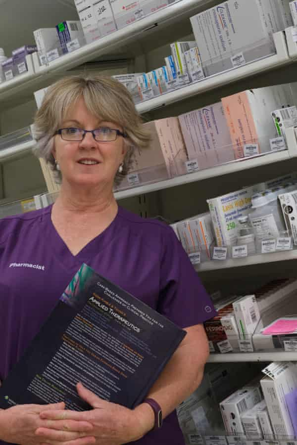 Kate Wood, in her pharmacist uniform, stands in front of shelves of medicine.