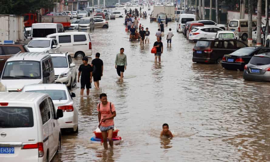 People wade through flood waters following heavy rainfall in Zhengzhou, China