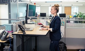 A woman standing at a desk in an office