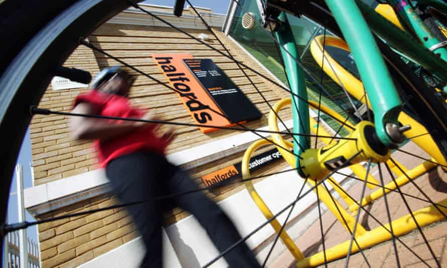 a picture of a cyclist leaving a Halfords store taken through the spokes of his bike