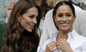 The Duchess of Cambridge (left) and the Duchess of Sussex chat in the royal box at Wimbledon's Centre Court.