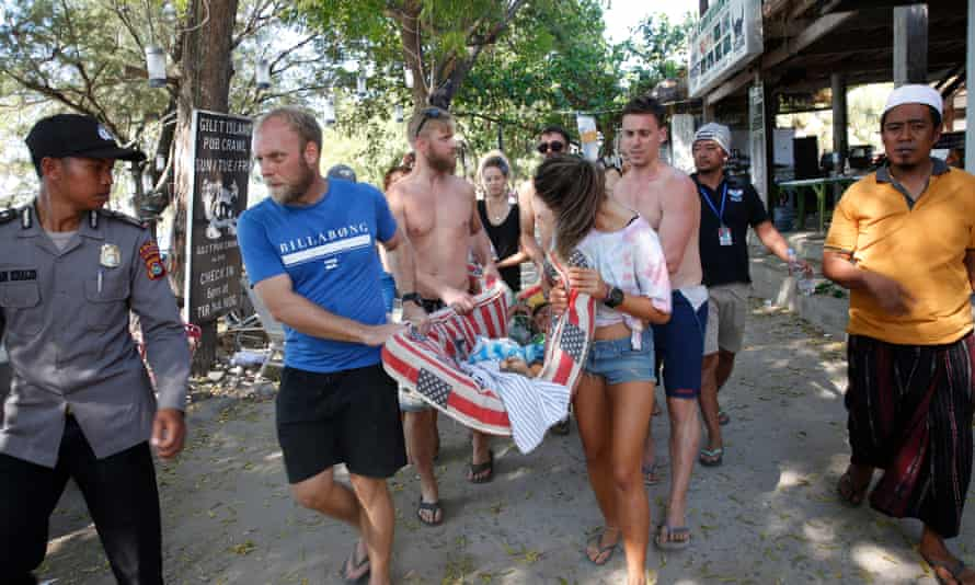 Foreigners on Gili Trawangan carry an Indonesian woman injured in the earthquake