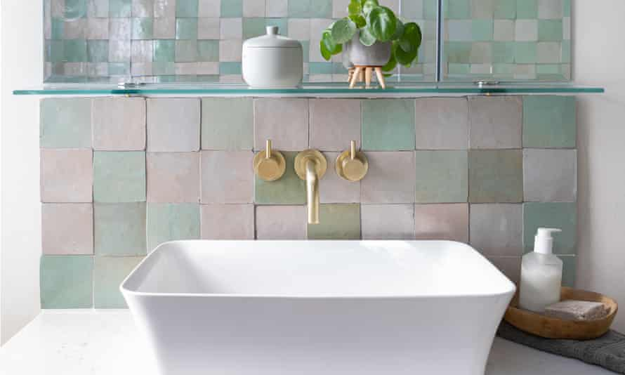 Square white kitchen sink with green and pink splashback tiles