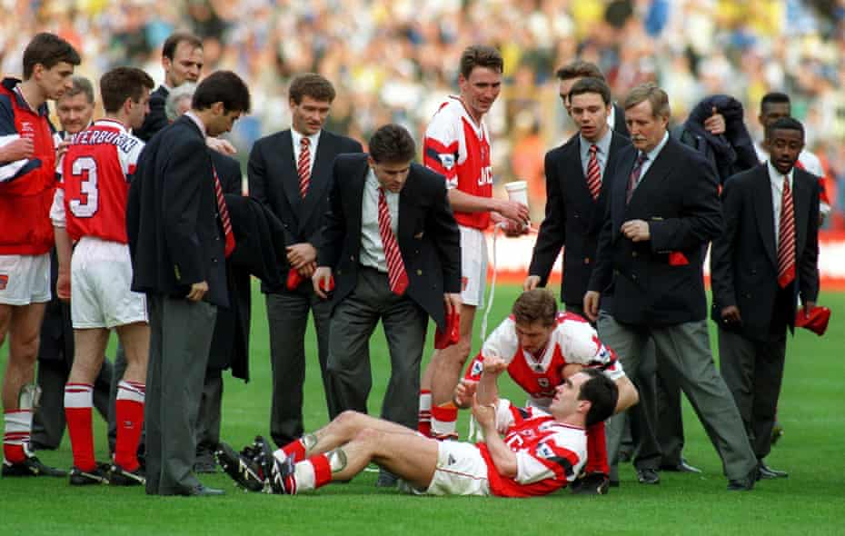 Steve Morrow holds his arm after being dropped by Tony Adams during the celebrations.