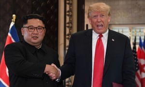 President Donald Trump (R) and North Korea's leader Kim Jong Un shake hands following a signing ceremony during their historic US-North Korea summit in June