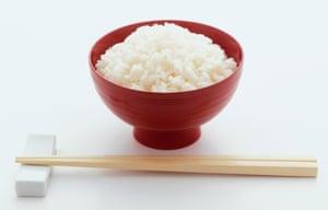Bol rouge de riz blanc nature et paire de baguettes devant.