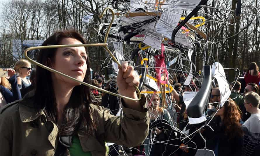A woman hangs up a coat hanger, symbolising illegal abortion