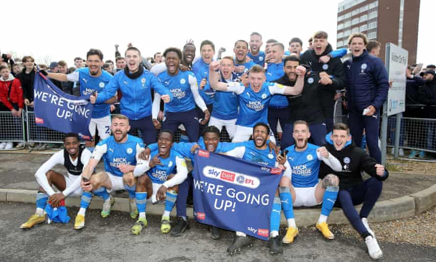 The Peterborough squad celebrate outside the ground after their late fightback secured a return to the Championship