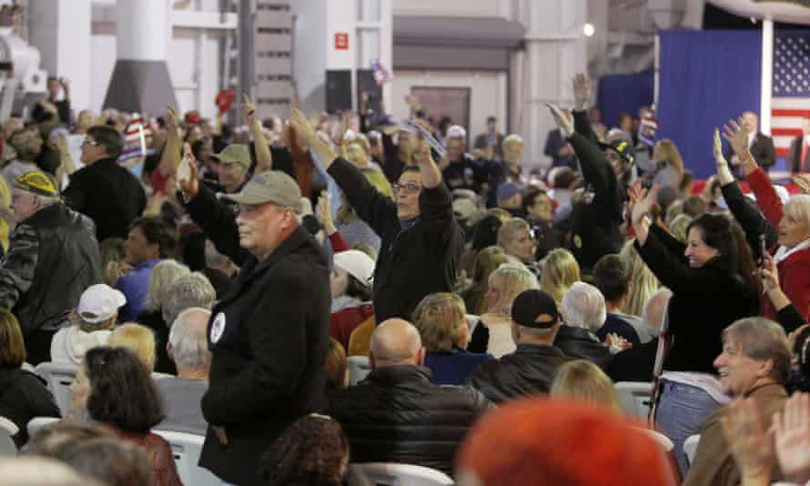 Supporters for Donald Trump wave to the press after being prodded by Republican presidential candidate.