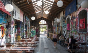 Waitress and patrons at a cafe at the Reitschule in Berne, a graffiti-covered complex that had once been a horse-riding school