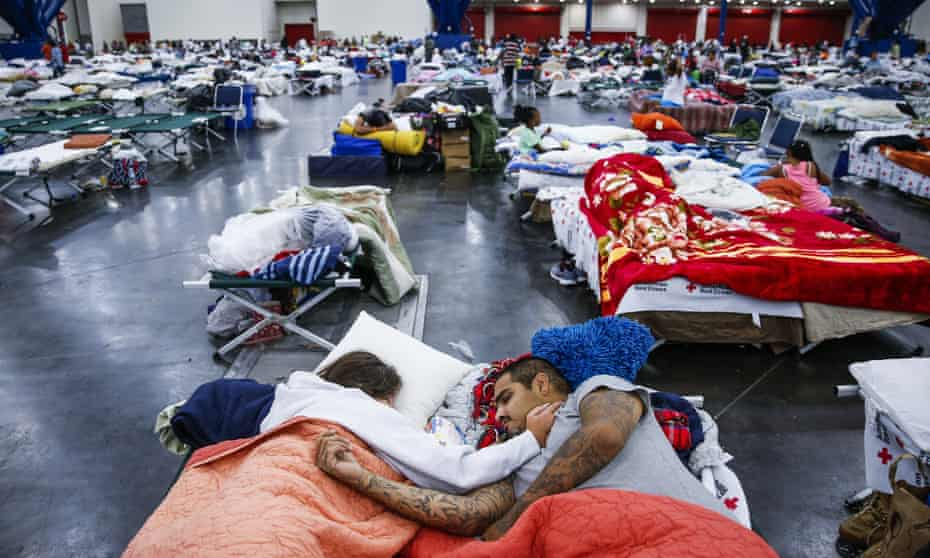 A couple sleeps on cots at the George R Brown Convention Center, where nearly 10,000 people are taking shelter.