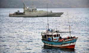 A navy patrol boat escorts a vessel carrying asylum seekers