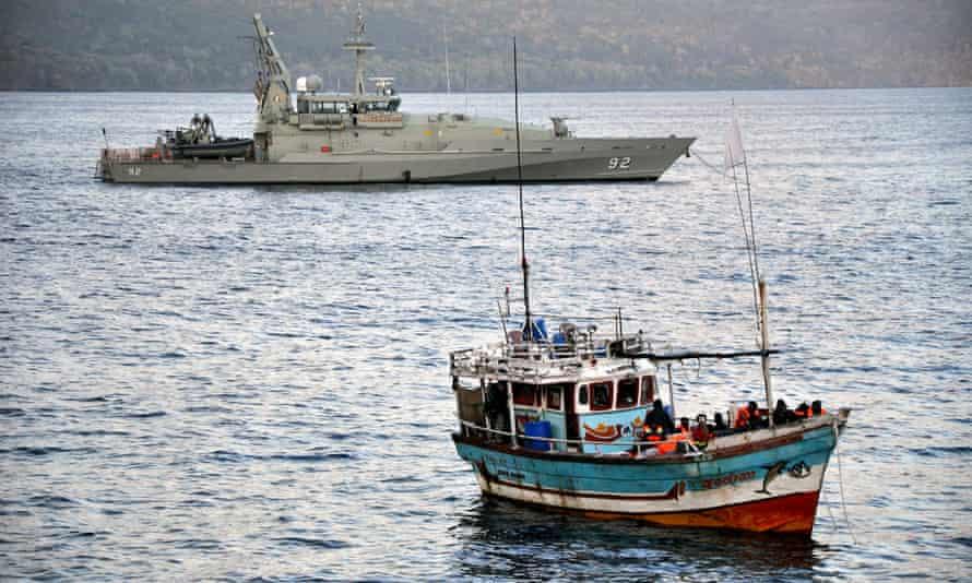 A navy patrol boat escorts a vessel carrying asylum seekers