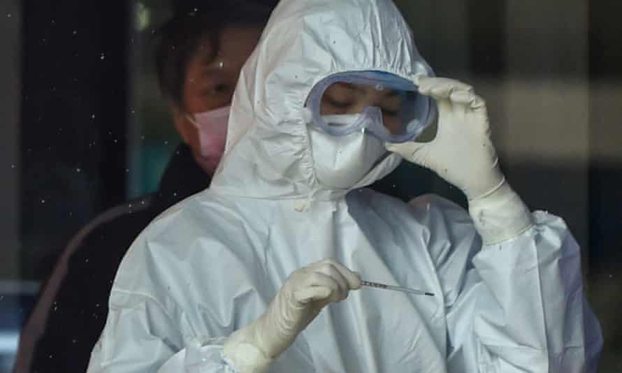 A nurse, wearing protective clothing to help stop the spread of the virus, reads a thermometer at the Wuhan Fifth hospital