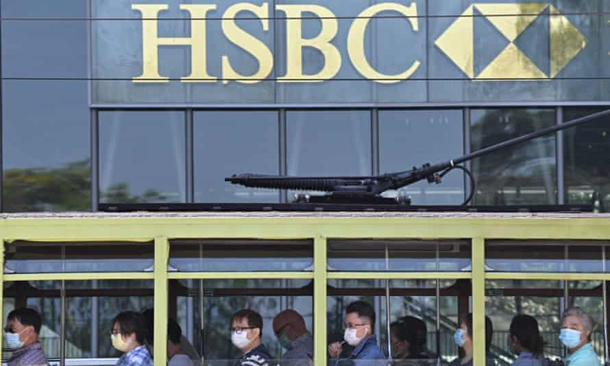 Commuters wearing face masks travel on a tram past HSBC signage displayed outside the banks local headquarters in Hong Kong