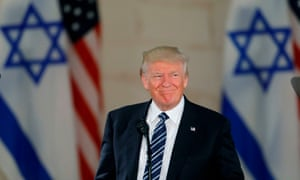 Donald Trump standing in front of Israeli and US flags.