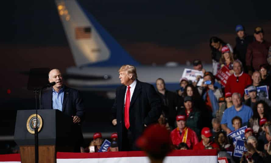 Donald Trump looks on as Greg Gianforte speaks during a campaign rally in Missoula, Montana on 18 October 2018.