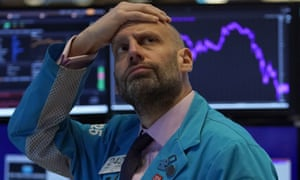 In this file photo taken on 9 March, 2020 Meric Greenbaum, Designated Market Maker IMC financial looks up at the board before the opening bell right before trading halted on the New York Stock Exchange on in New York.