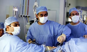 Lord Darzi, centre, performing surgery.