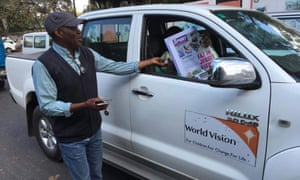 Taking to the streets: The Post's editor-in-chief, Fred M'membe, sells copies of his paper following the seizure of its assets.