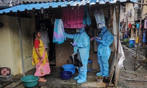 Healthcare workers in Mumbai take the temperature of a woman as part of efforts to tackle coronavirus in India.