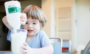 Boy pouring glass of milk