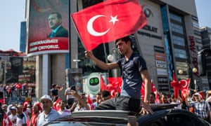 A man waves a Turkish flag from a car roof during a march in Kizilay Square, Ankara